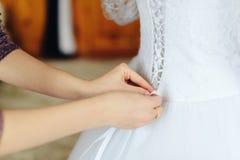 L'amie aide la jeune mariée à lacer le corset, rassemblements de matin de la jeune mariée Image stock