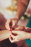 L'amie aide le bracelet de bouton de jeune mariée Photo stock