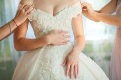 L'amie du ` s de jeune mariée aide la jeune mariée à habiller sa robe de mariage photographie stock libre de droits