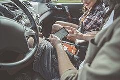 L'amie et l'ami positifs ouvrent le système de navigation Photo stock