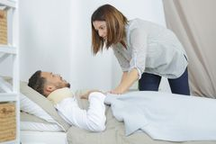 L'amie salut le malade d'homme dedans sur le lit Image libre de droits