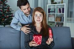 L'amie semble sceptique à son cadeau de Noël Photos libres de droits