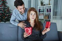 L'amie semble sceptique à son cadeau de Noël Photographie stock libre de droits