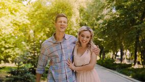 L'amie souriant sincèrement, les couples heureux marchant en été se garent, date romantique Image stock