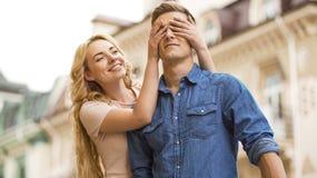 L'amie venant par derrière les amis et couvrants observe, surprise romantique Images libres de droits