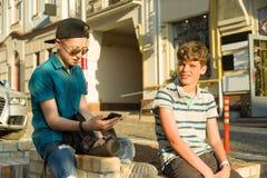 L'amitié et la communication de deux adolescents est 13, 14 années, fond de rue de ville Photos libres de droits