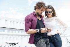 L'amitié heureuse de couples avec le téléphone portable et la vitesse fixe vont à vélo Photo libre de droits