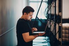 L'amministratore di sistema delle free lance lavora al computer portatile immagini stock