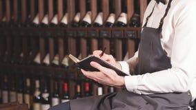 L'amministratore di vino maschio esamina le bottiglie di vino e di scrittura in taccuino il deposito di vino archivi video