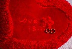 L'amore è… indicatore di rosa su fondo bianco Immagini Stock Libere da Diritti