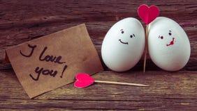 L'amore di due uova, di cuori rossi e della carta con testo ti amo Fotografia Stock