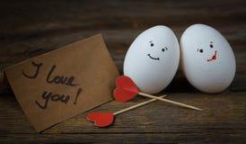 L'amore di due uova, di cuori rossi e della carta con testo ti amo Fotografie Stock