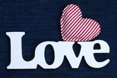 L'amore di parola con cuore rosso sul fondo del denim Immagine Stock
