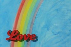 L'amore di parola con un fondo variopinto del cielo blu e dell'arcobaleno Immagine Stock
