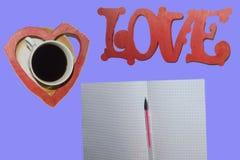 L'amore di parola, una tazza di caffè, un cuore, una foglia con una penna immagine stock