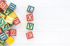L'AMORE scrive in blocchetto di legno dell'alfabeto su fondo di legno bianco fotografie stock