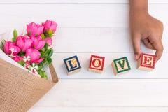 L'AMORE scrive in blocchetto di legno dell'alfabeto su fondo di legno bianco fotografie stock libere da diritti