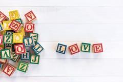 L'AMOUR écrivent dans le bloc en bois d'alphabet sur le fond en bois blanc Photographie stock libre de droits