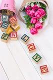 L'AMOUR écrivent dans le bloc en bois d'alphabet sur le fond en bois blanc Photo libre de droits