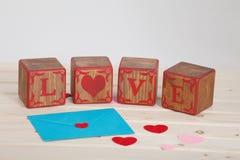 L'AMOUR écrivent dans le bloc en bois d'alphabet sur le fond lumineux de conseil Concept ou Saint Valentin d'amour Image stock
