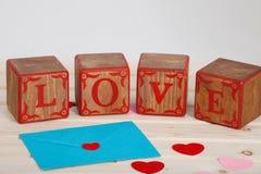 L'AMOUR écrivent dans le bloc en bois d'alphabet sur le fond lumineux de conseil Concept ou Saint Valentin d'amour Photographie stock libre de droits