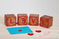 L'AMOUR écrivent dans le bloc en bois d'alphabet sur le fond lumineux de conseil Concept ou Saint Valentin d'amour Photos stock