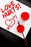 L'amour blesse le texte peint sur un papier blanc Images libres de droits