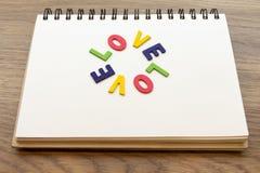 L'amour coloré en bois de mot de lettre fixent le carnet sur le bureau en bois Co Image libre de droits