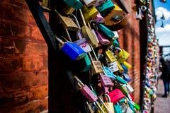 L'amour coloré ferme à clef sur un fond de brique rouge Photos stock