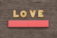 L'AMOUR a défini avec des biscuits sur le dessus d'un conseil en bois gris Photographie stock