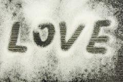 L'amour d'inscription sur le sucre a dispersé sur un fond foncé en bois Photographie stock