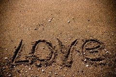 L'AMOUR d'inscription sur un littoral humide de sable modifié la tonalité Image stock