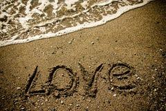 L'AMOUR d'inscription sur un littoral humide de sable modifié la tonalité Images libres de droits