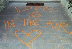 L'amour de ` de signe est dans le ` d'air sur le trottoir Photo stock