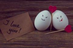 L'amour de deux oeufs, de coeurs rouges et de carte avec le texte je t'aime Photographie stock libre de droits