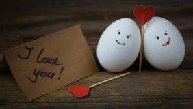 L'amour de deux oeufs, de coeurs rouges et de carte avec le texte je t'aime Image libre de droits