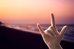L'amour de mains se connectent la plage de coucher du soleil Photographie stock