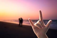 L'amour de mains se connectent la plage de coucher du soleil Images stock