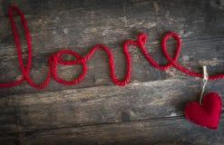 L'amour de mot écrit avec un fil de laine rouge et le coeur des clo Photo libre de droits