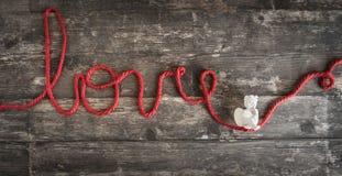 L'amour de mot écrit avec un fil de laine rouge où un ange est Photo stock