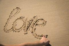 L'amour de mot écrit dans le sable Photographie stock