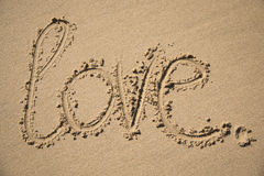 L'amour de mot écrit dans le sable Photos libres de droits