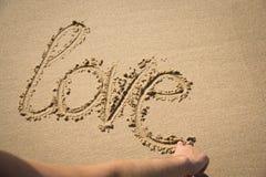 L'amour de mot écrit dans le sable Image libre de droits