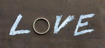 L'amour de mot écrit sur le tableau avec une lettre remplacée par un anneau Photo stock