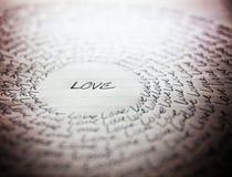L'amour de mot écrit sur un morceau rayé de papier d'école Photo stock