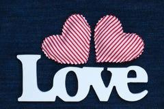 L'amour de mot avec des coeurs sur le contexte bleu de denim Photos libres de droits