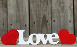 L'amour de mot avec deux coeurs rouges Photographie stock