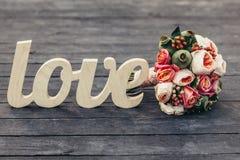 L'amour de mot avec le beau bouquet de mariage sur le backgrou en bois Photo libre de droits
