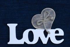 L'amour de mot avec le coeur en bois sur le fond bleu de denim Photographie stock libre de droits