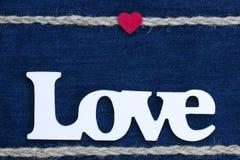 L'amour de mot avec le coeur et la frontière de corde sur le denim Photo libre de droits